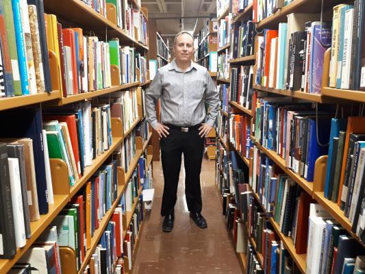 Image of Dave Yott among the stacks at Leddy Library
