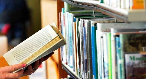 open library book being held in front of book shelf