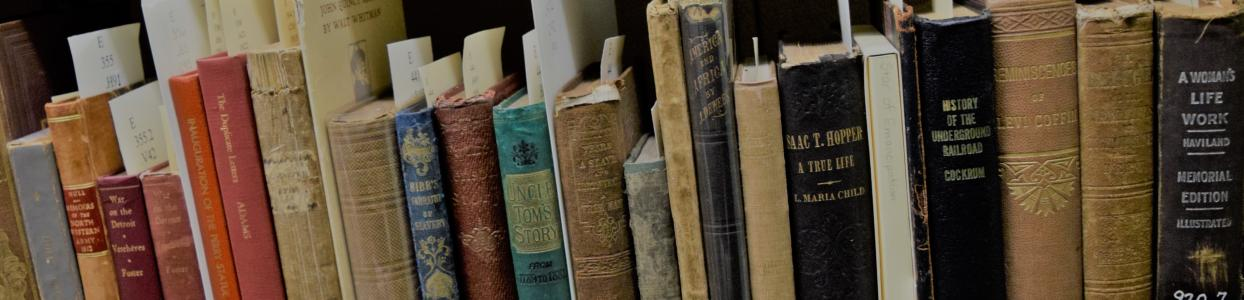 Close-up of the colourful spines of old books on a library shelf.